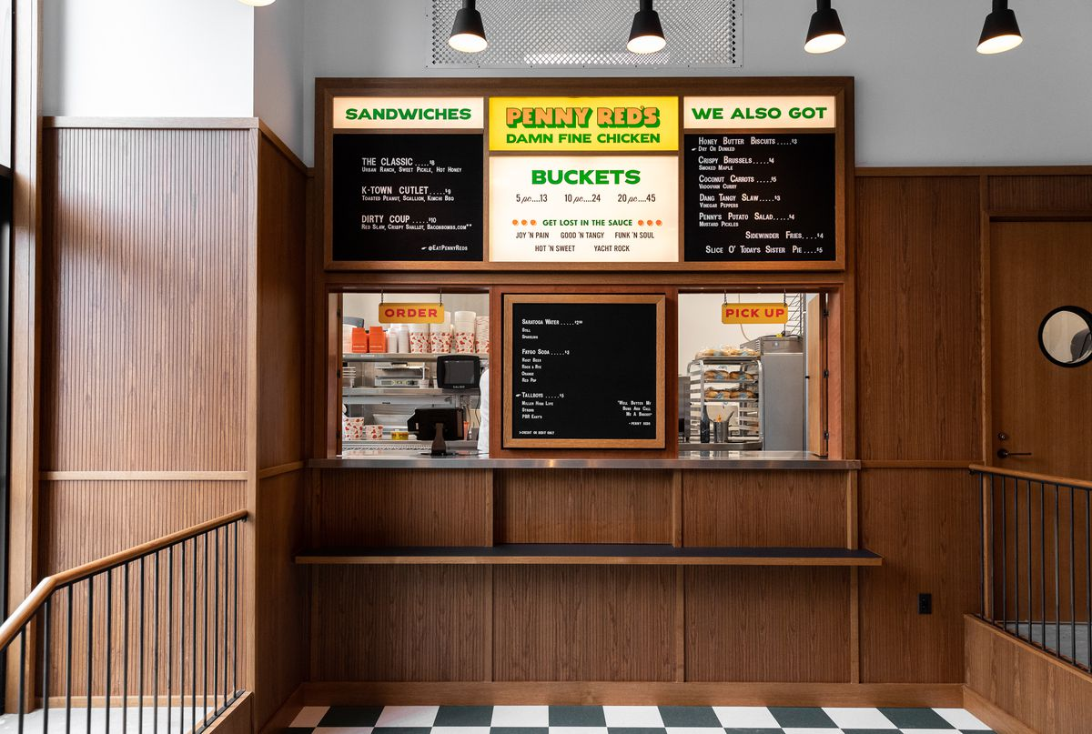 The ordering window and menu board at penny red's has a mid-century look with wood paneling