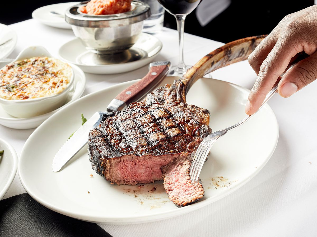 A large tomahawk steak, partially eaten, on a plate with a knife. The white-tablecloth covered table also includes asparagus, creamed corn, and a glass of red wine. A hand reaches a fork in from the side of the frame to take a bite of the steak