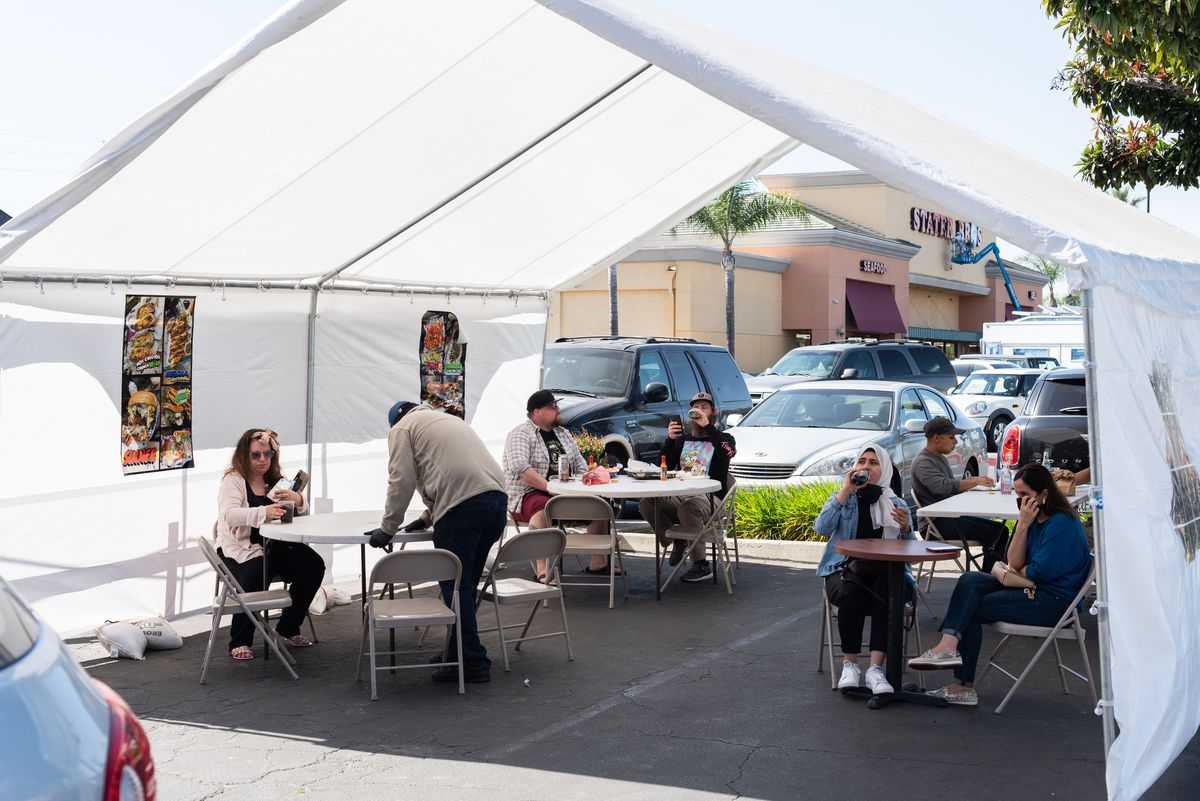 Customers gather under a tent to eat food in a parking lot.