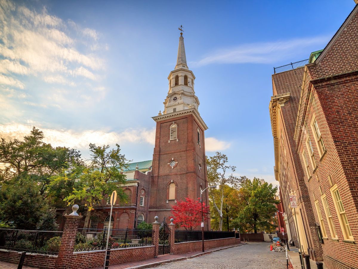 The exterior of Christ Church in Philadelphia. The facade is red brick and there are trees in a courtyard in front.