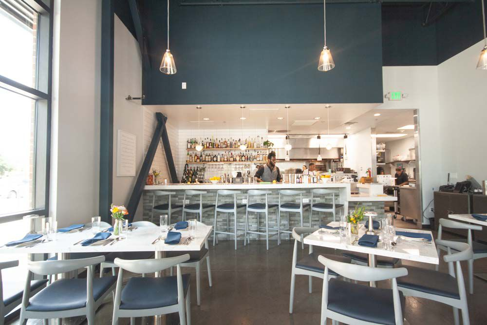 A restaurant dining room with white and blue chairs, white tables, and pendant lighting hanging from the ceiling