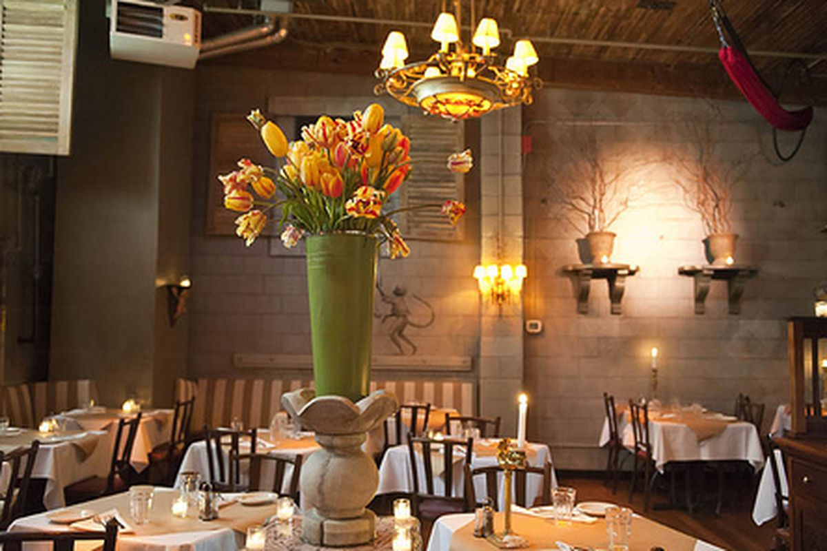 The interior of The Pink Door with flowers and chandeliers in the dining room.
