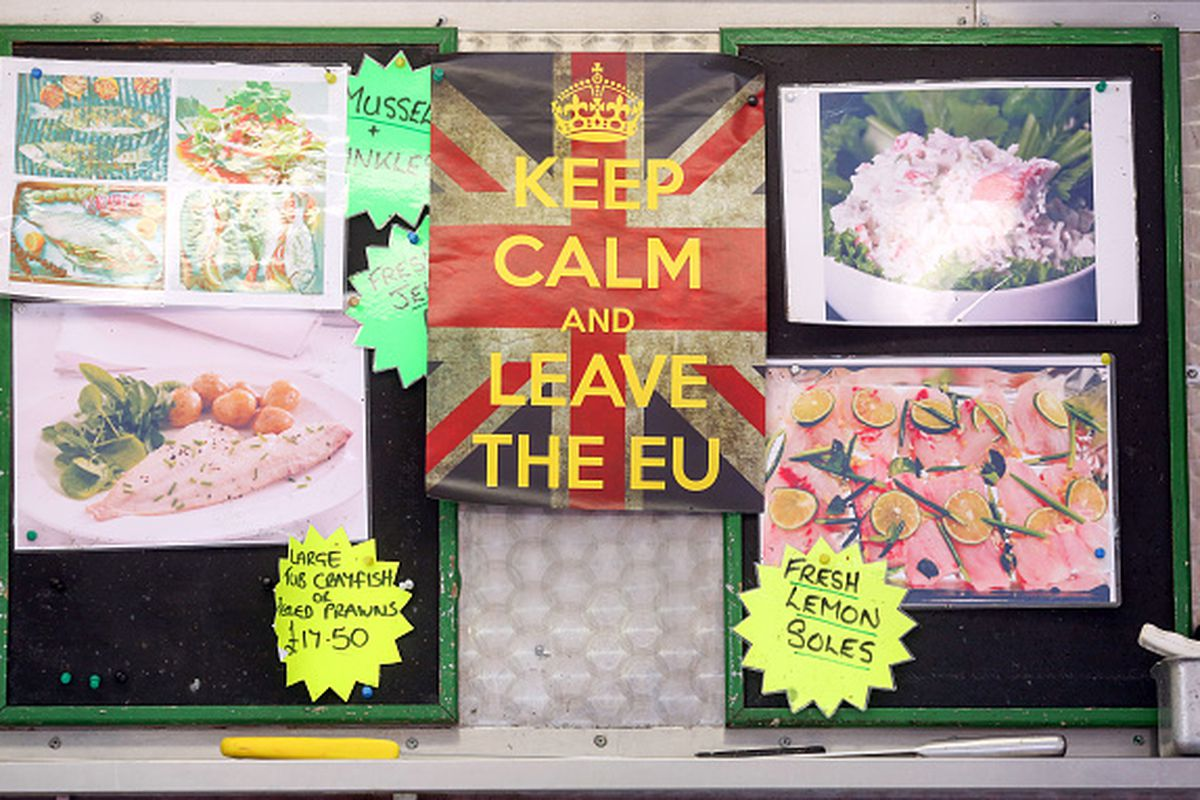 """A """"leave EU"""" campaign poster, which reads """"Keep Calm and Leave the EU,"""" hangs behind Dave Crosbie's fishmonger stall at the market in Romford, UK, on March 30, 2016."""