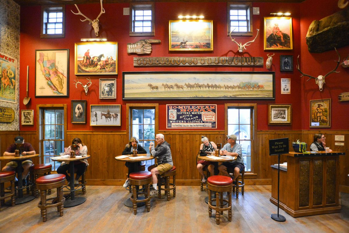 Diners at small bar tables sit inside of a Western themed bar.