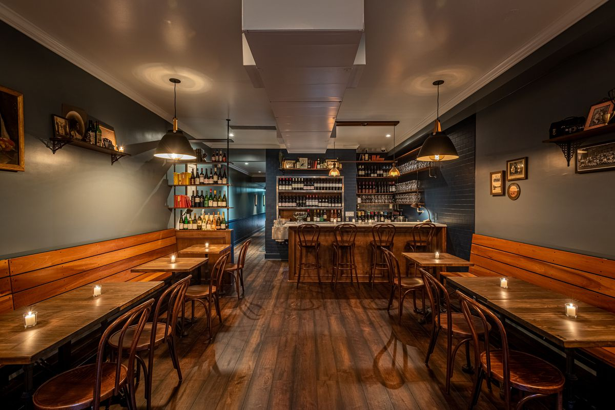A long, narrow room with a wine bar at the end and wood seating.