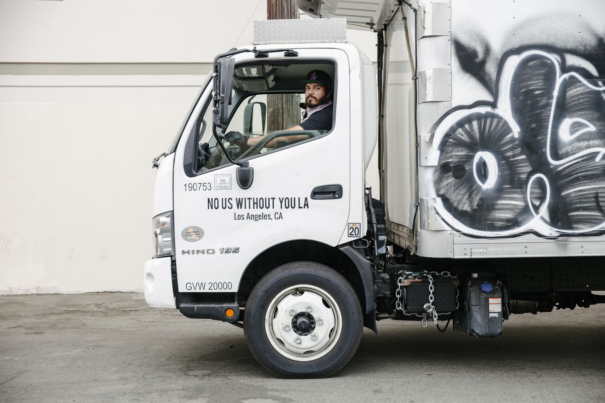 Bearded man with baseball cap looks out from the cab of a truck.