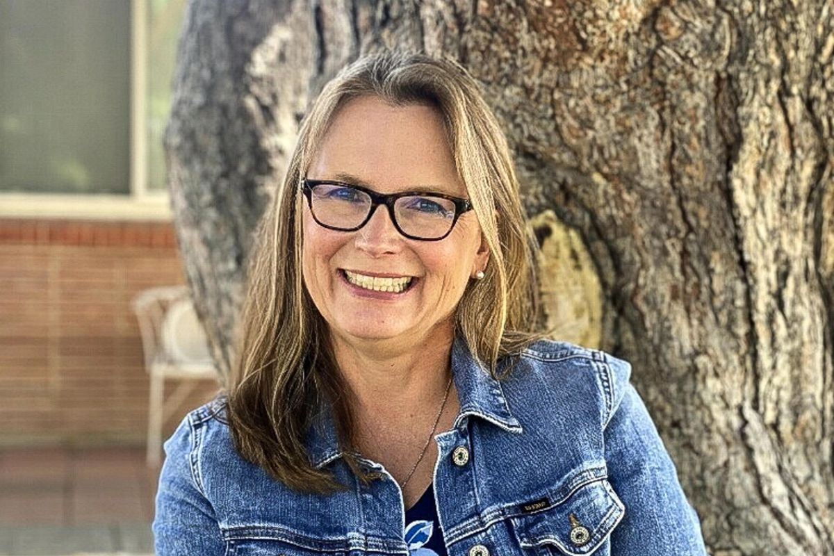 A portrait of Denver school board candidate Carrie Olson, who is sitting against a tree wearing denim jacket and glasses.