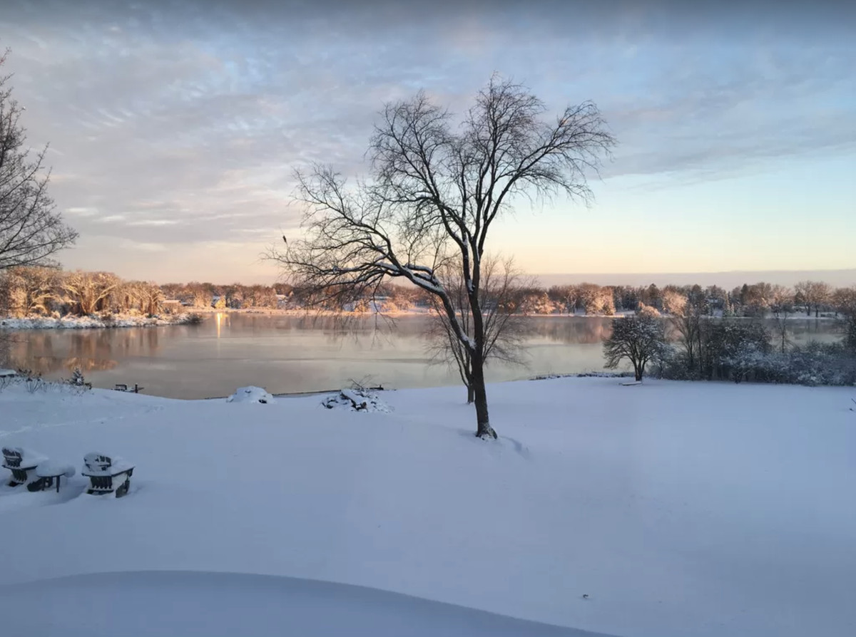 A view outside the property shows a serene lake with a snow covered yard.