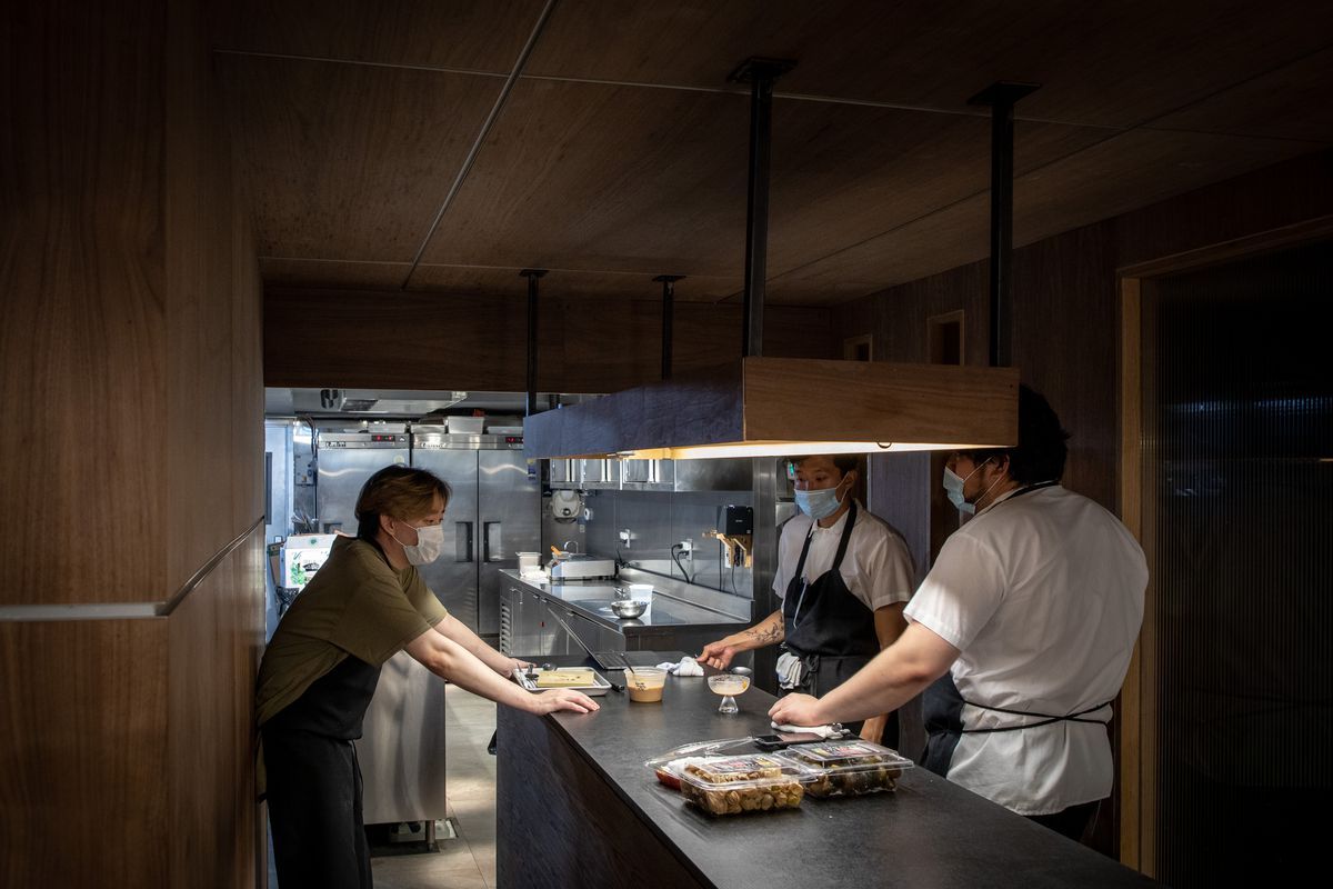 Three chefs in masks taste test food in a kitchen.