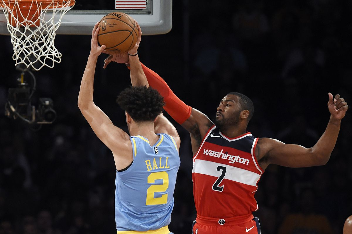 Lonzo Ball attempts a shot while being defended by John Wall
