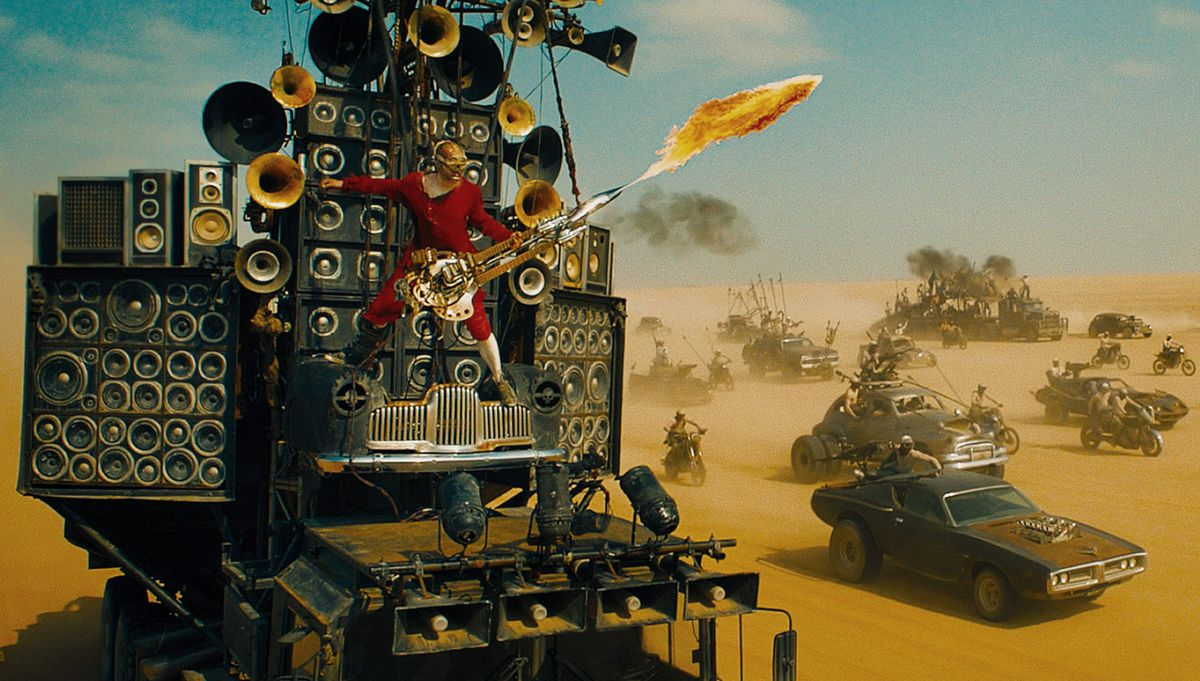 doof warrior stands on the speaker truck playing his fire guitar in the desert