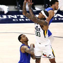 Utah Jazz guard Jordan Clarkson (00) puts in a shot over Dallas Mavericks guard Trey Burke (3) as the Utah Jazz and the Dallas Mavericks play an NBA basketball game at Vivint Smart Home Arena in Salt Lake City on Wednesday, Jan. 27, 2021.