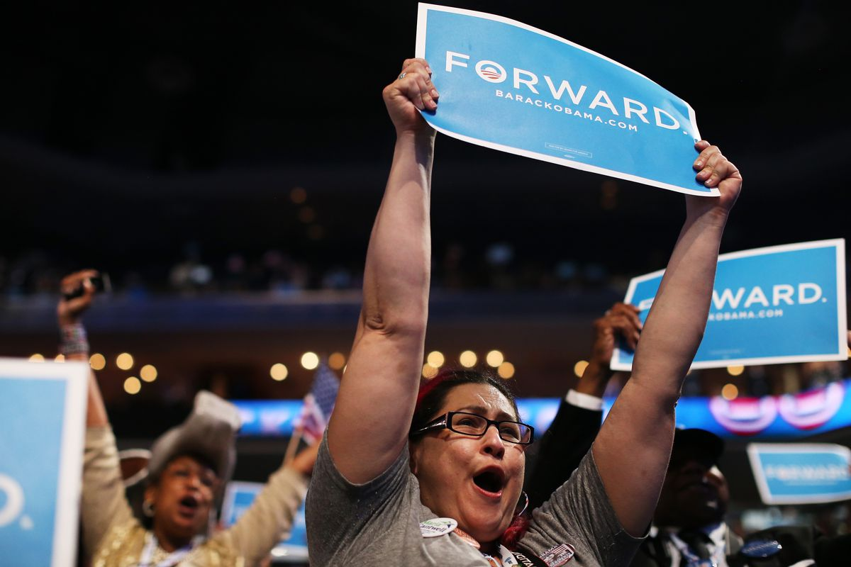 """A woman holds up a """"Forward"""" sign and cheers as Barack Obama accepts the Democratic nomination for president in 2012."""