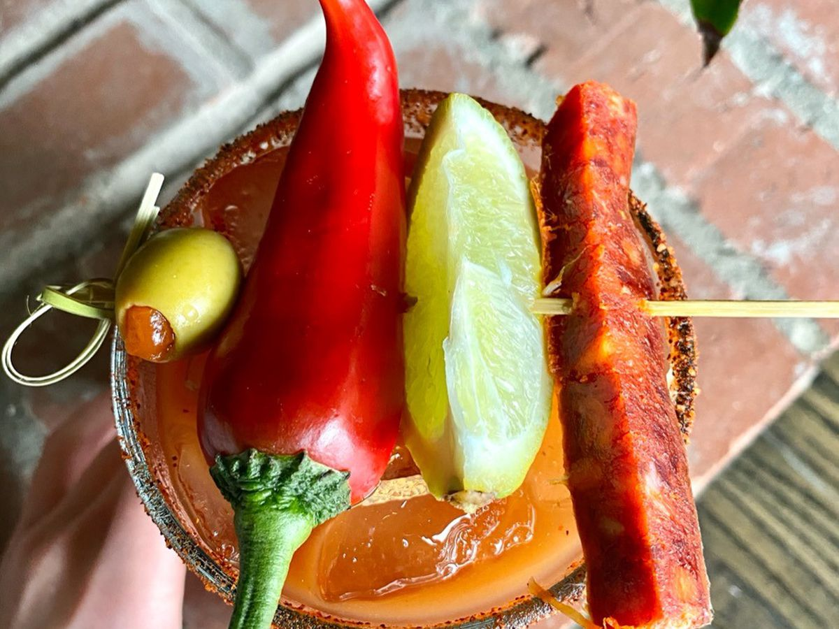 A bloody mary viewed from the top, garnished with lime wedge, olive, fresno pepper, and chorizo sausage