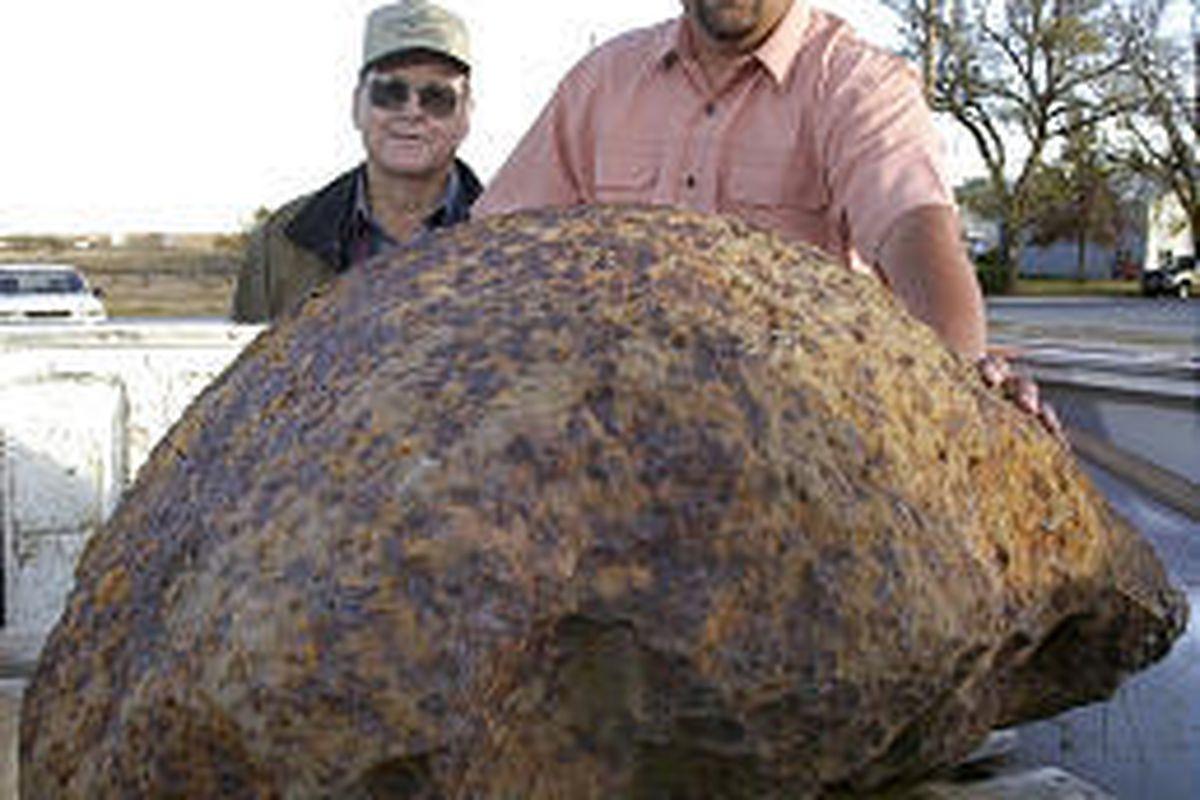Steve Arnold, right, shows off rock he found on the farm of Allen Binford, left, in Haviland, Kan.