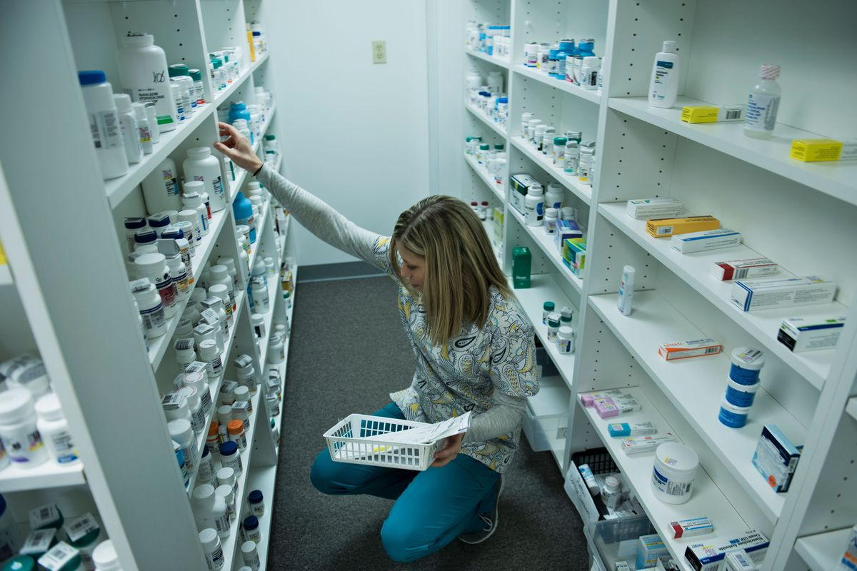 A pharmacist reaching for medications in an aisle lined with shelves.