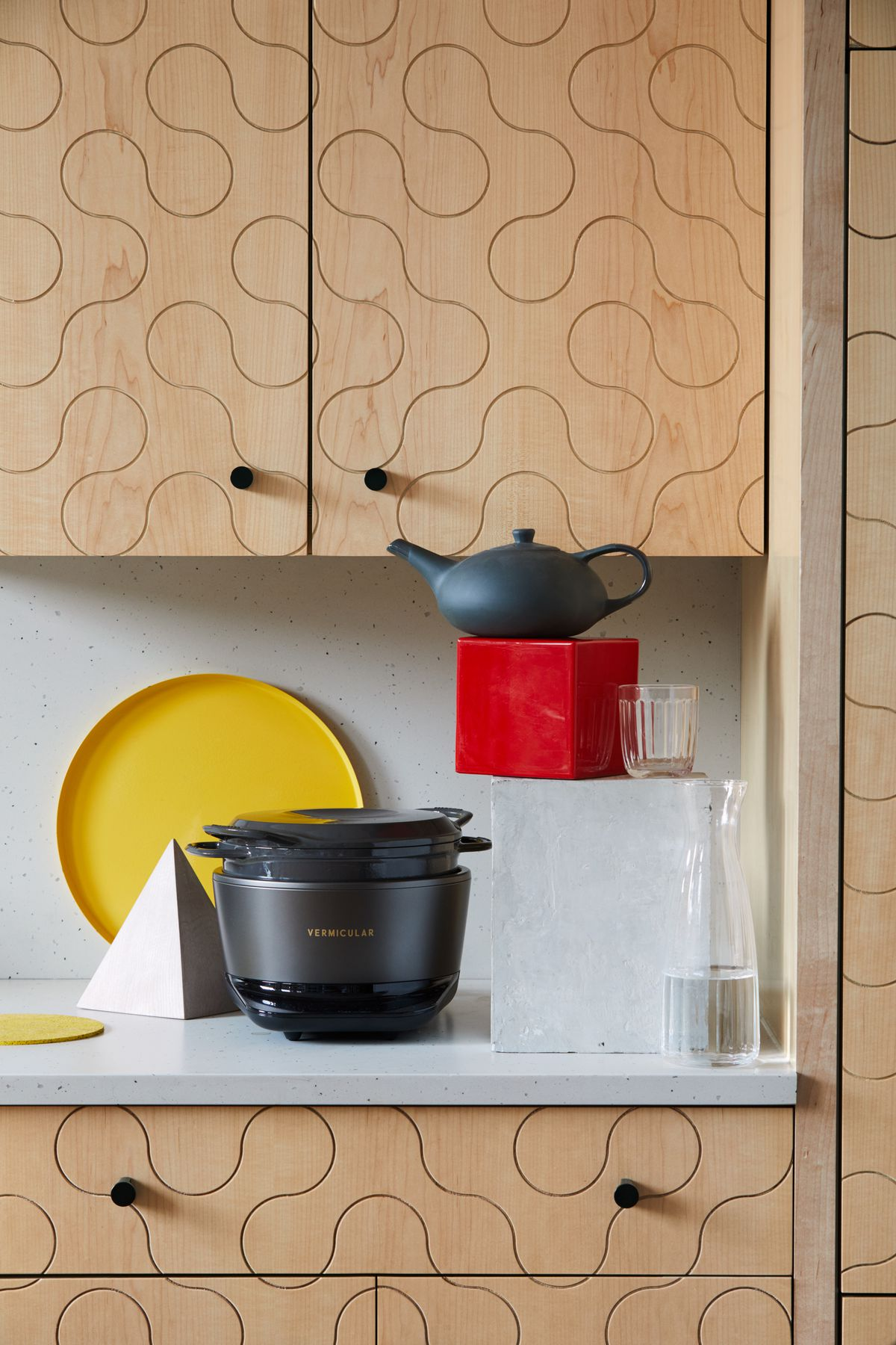 Cookware, a teapot, and a tumbler arranged on a kitchen countertop.