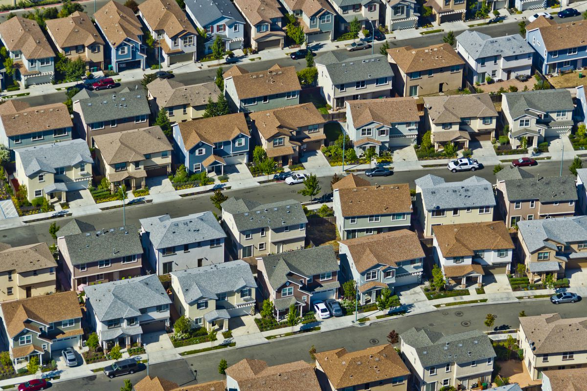 An aerial view of a suburban subdivision filled with two-storey single-family houses.