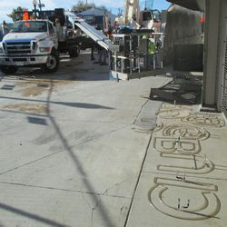 1:50 p.m. A wide view of the scene in front of Gate D, with the neon letters on the ground -