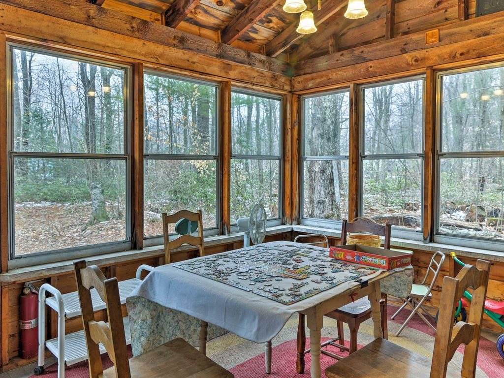 A sunroom in the woods, with several windows and a table in the middle with a puzzle out on top of it.