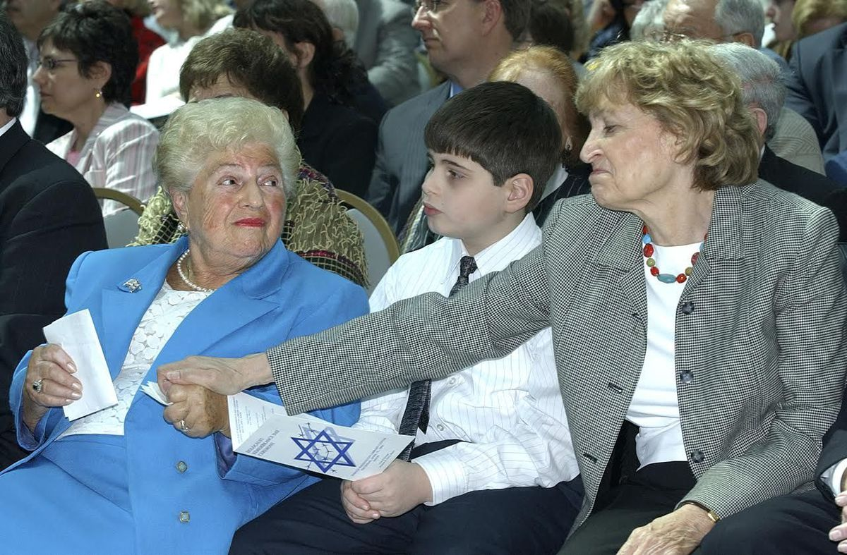 At a 2005 Holocaust Remembrance Day ceremony at the Harold Washington Library, Holocaust survivors Barbara Steiner (left) and Fritzie Fritzshall shared a moment. Mrs. Steiner was the keynote speaker. Her grandson Robby Blumstein sat between them.   Sun-Ti