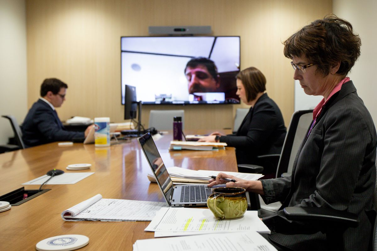 Prosecutors Kristin Zimmerman, Breanne Miller and Alex Stoedter, from right to left, participate in a remote hearing with Judge Barry Lawrence, appearing on screen, in a conference room at the Salt Lake County District Attorney office building in Salt Lake City on Friday, March 27, 2020.Utah's criminal justice system is trying several new things in order to keep the courts running amid the novel coronavirus outbreak.
