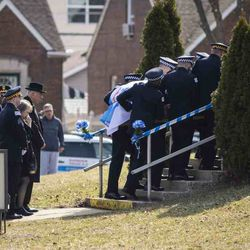 Family follows closely behind as pallbearers carry in the casket for Chicago Police Officer John P. Rivera before the start of his funeral at the Church Of Annunciata on the Far South Side, Friday morning, March 29, 2019. | Ashlee Rezin/Sun-Times