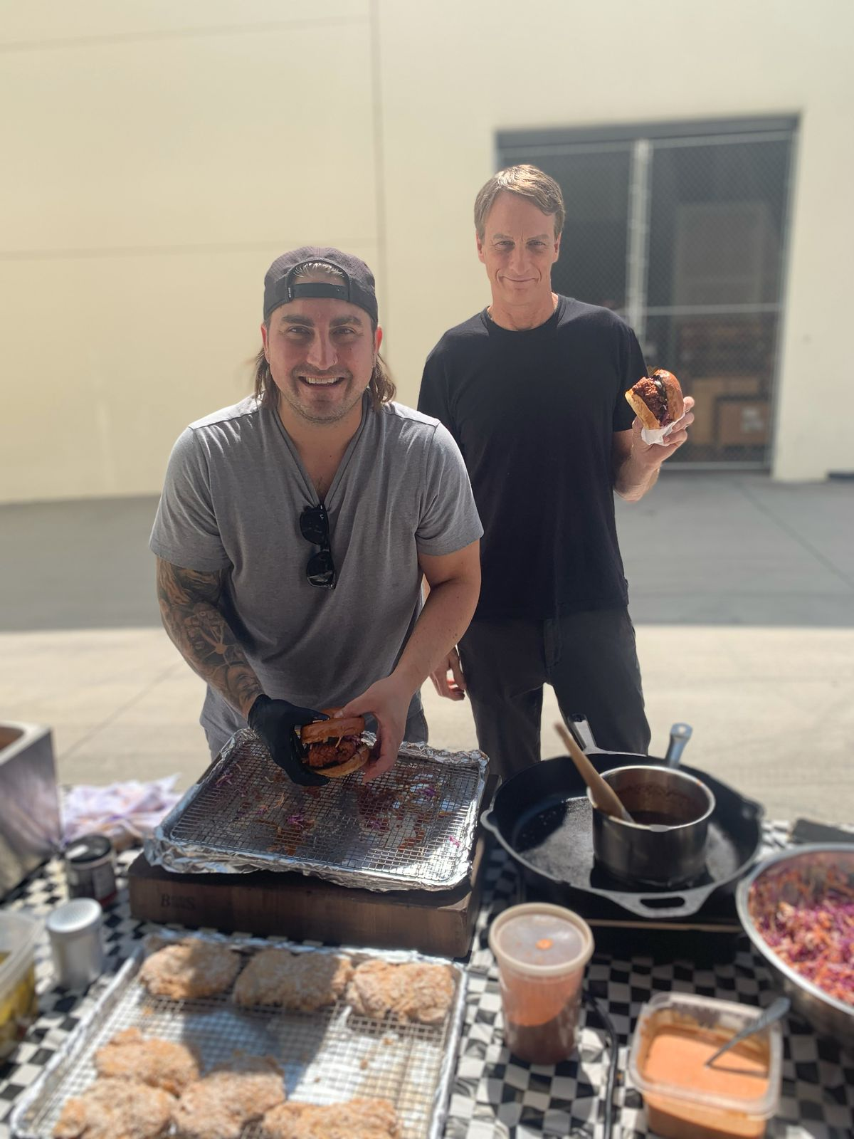 Chef Andrew Bachelier assembles fried chicken sandwiches while Tony Hawk stands behind him holding a sandwich.