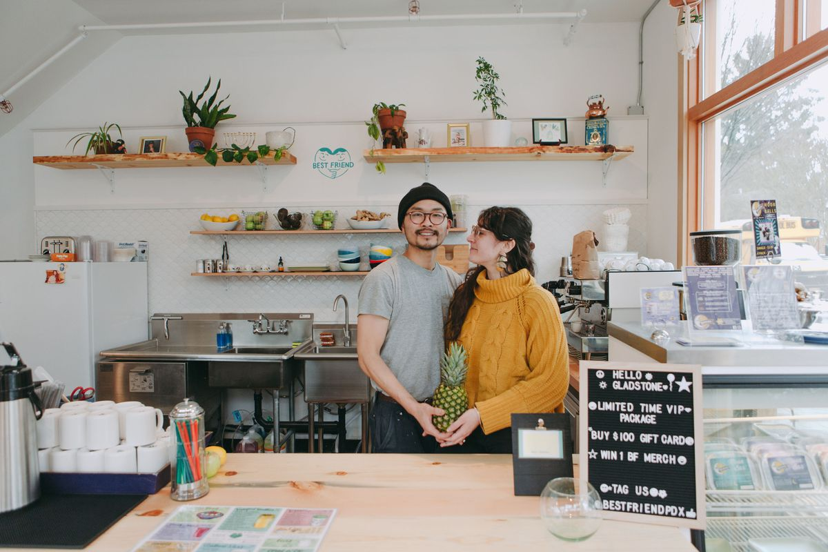 A man in glasses and a grey shirt holds the hand of a woman with long brown hair in a yellow sweater. They stand behind the counter of a white-walled cafe with shelves of plants. A coffee canister and mugs sit just out of frame