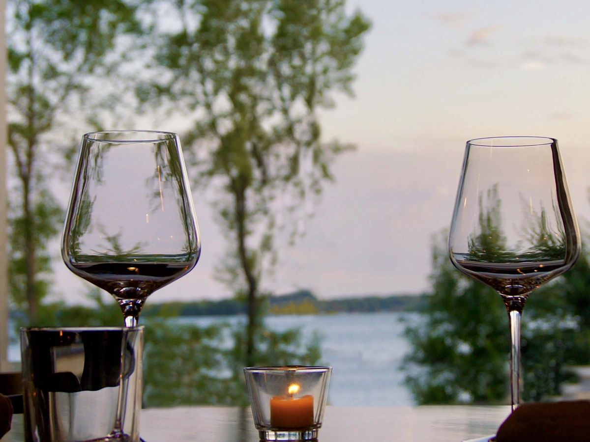 Two wine glasses and a lit votive are set on a table looking out a window at a brilliant blue stretch of lake