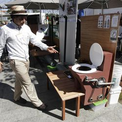 """Marcos Fiovavanti, of the Ecuador-based """"Fundacion In Terris"""" group, talks about the """"Earth Auger Toliet,"""" which is operated by a mechanical pedal and chain system, on display at the """"Reinventing the Toliet"""" Fair, Tuesday, Aug. 14, 2012, in Seattle, which is part of a Bill & Melinda Gates Foundation competition to reinvent the toilet for the 2.6 billion people around the world who don't have access to modern sanitation. (AP Photo/Ted S. Warren)"""