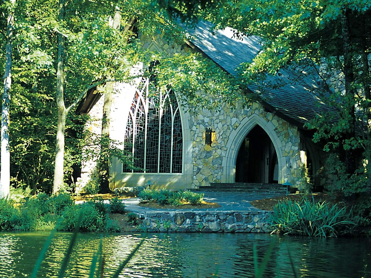 A stone building with a sloped roof surrounded by trees. There is a body of water in front of the building.