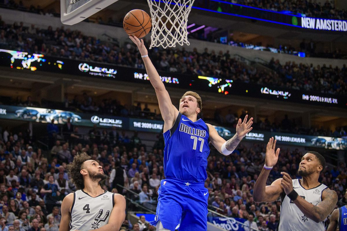 Dallas Mavericks forward Luka Doncic drives to the basket past San Antonio Spurs guard Derrick White and forward Rudy Gay during the second half at the American Airlines Center.