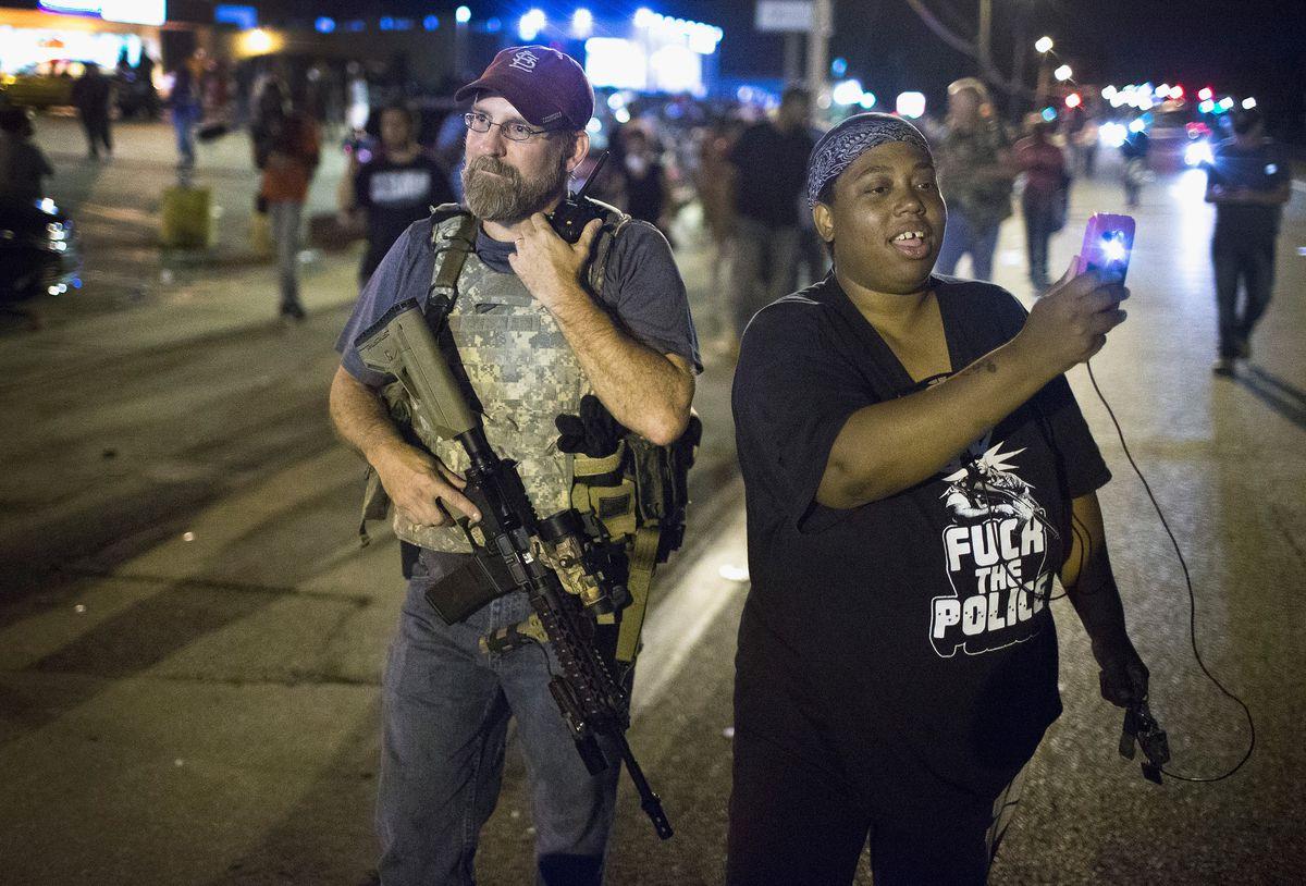 A protester takes a selfie by an Oath Keeper in Ferguson.
