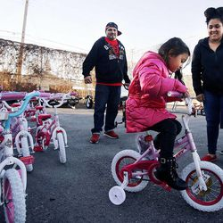 Volunteer Pat Archibeque, left, helps as Meilissa Ramirez tries out a new bike during 2014 Operation Chimney Drop at Head Start in Salt Lake City, Monday, Dec. 15, 2014. At right is Meilissa's mother, Jeanette Ramirez.