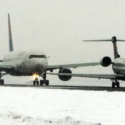 Jets line up to take off from Salt Lake City International Airport during a snowstorm, Thursday, Dec. 19, 2013.