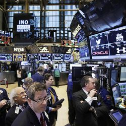 FILE - In this Wednesday, Feb. 12, 2014, file photo, traders monitor stock prices at the New York Stock Exchange. Stocks were mostly higher in midday trading Tuesday, Feb. 18, 2014, as investors returned from a long holiday weekend.