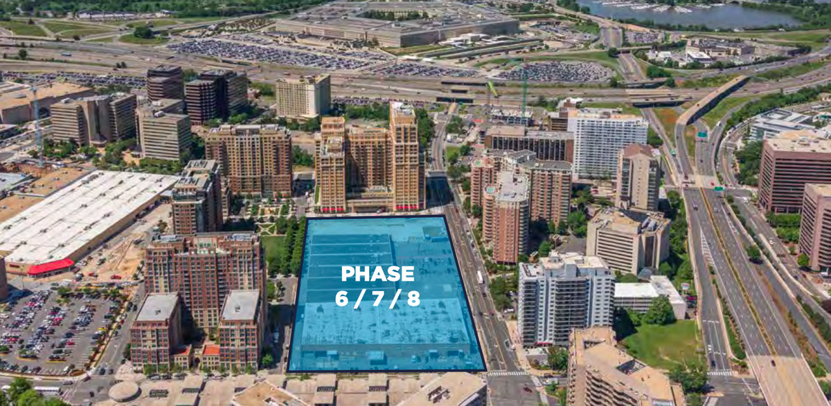 A photo of a development site overlaid with a blue rectangle. The site is surrounded by tall buildings.