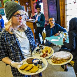 Daisy Alexander carries plates of fresh breakfast to a table at Home Grown.