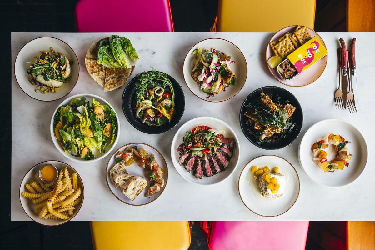nhiều đĩa thức ăn trên nền trắng, hồng và vàng