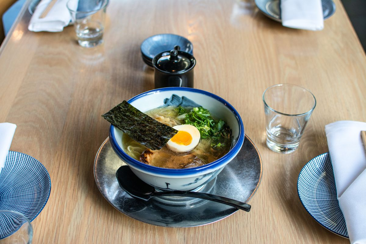 A blue bowl of ramen sits on a blonde wood table. The bowl comes with a half of a boiled egg, a sheet of green-black nori, and a pile of greens.