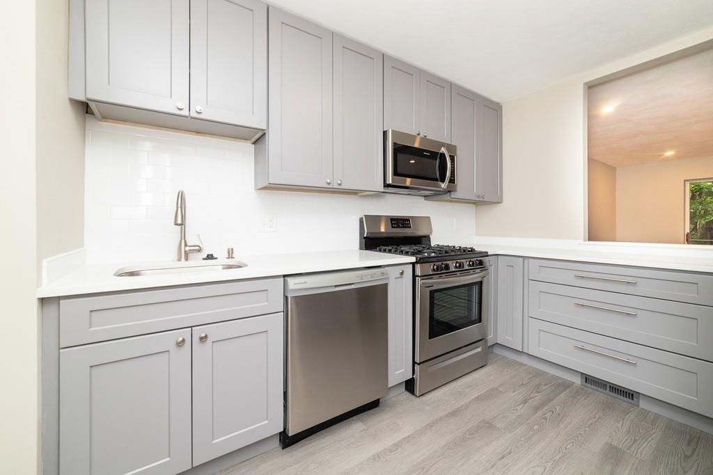 A renovated kitchen with new cabinetry and an L-shaped counter.