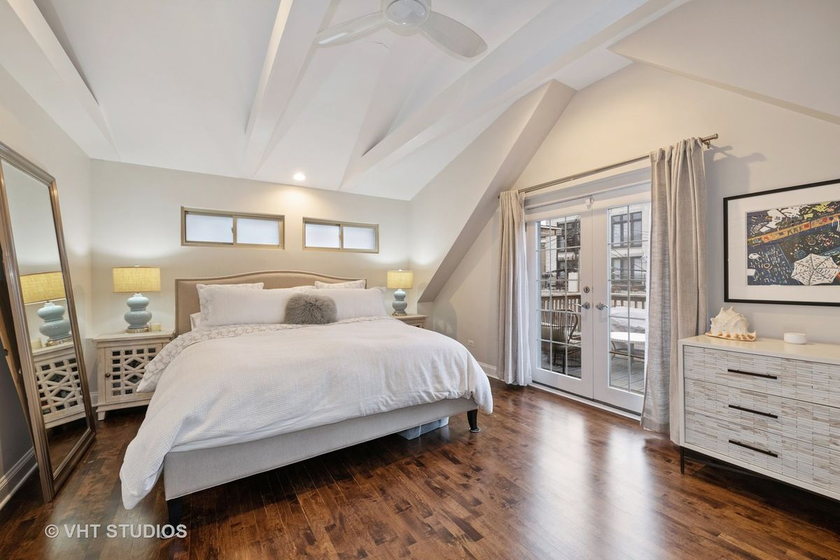 A bedroom with a bed, French doors, a dresser, two night stands, and a beamed ceiling.