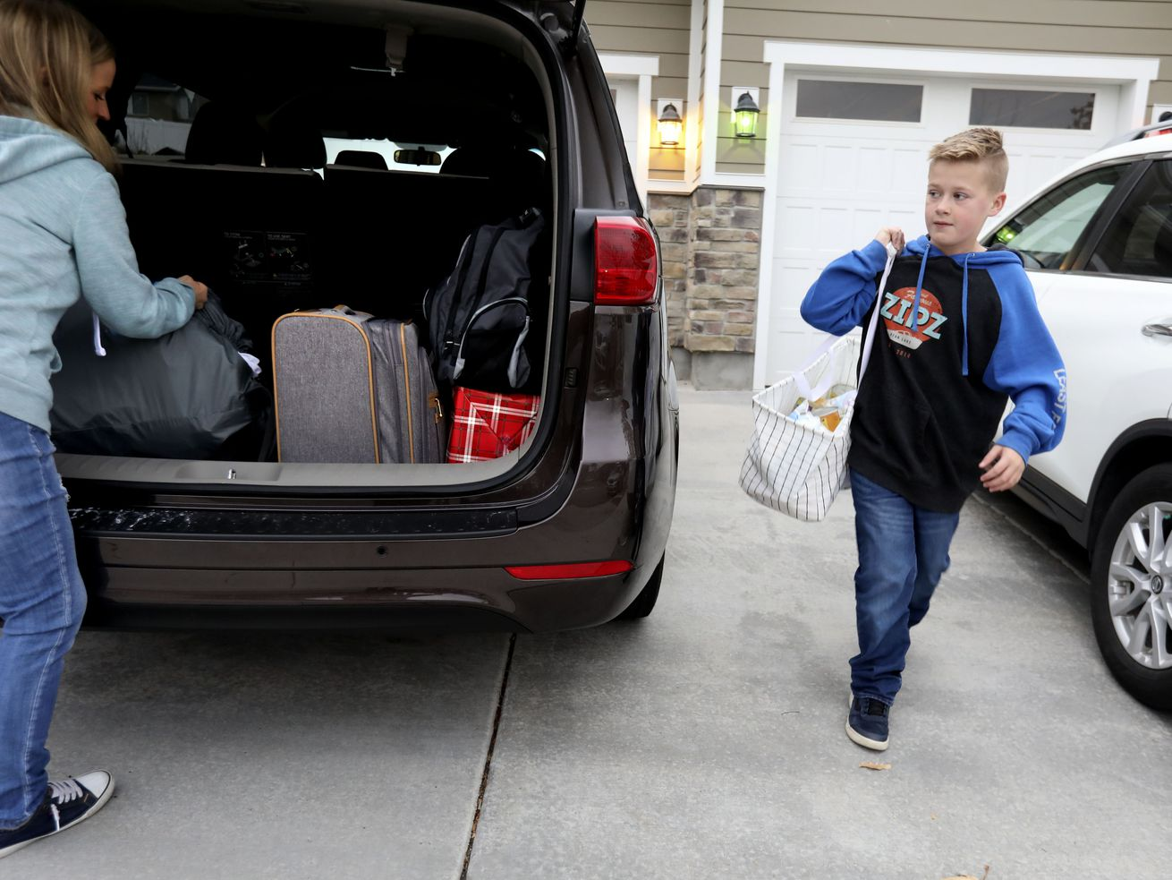 Bryce Spindle, 11, and his mother, Kendra, pack the car at their Herriman home before driving to Arizona on Friday, Nov. 22, 2019.