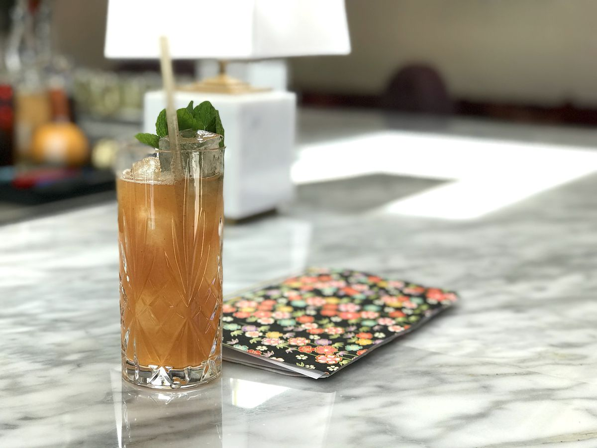 Rum cocktail with guava and lime on marble bartop