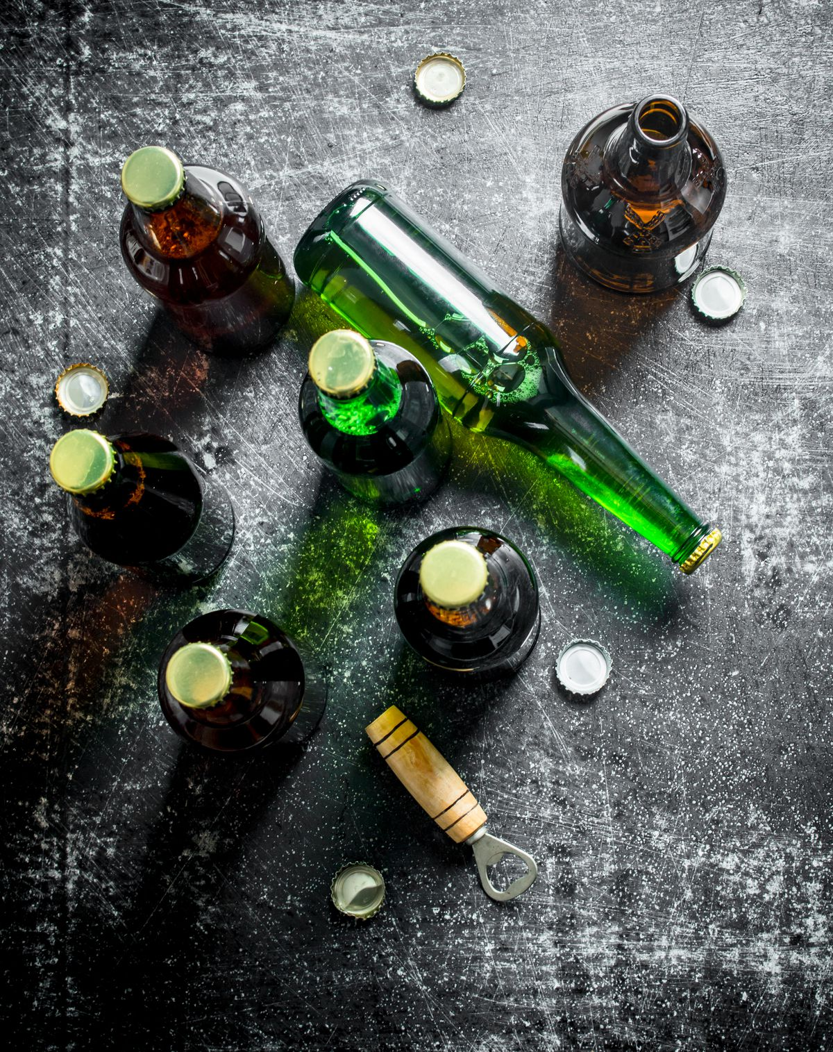 Seven beer bottles, some empty and some full, sit on a table with bottle caps and a bottle opener.