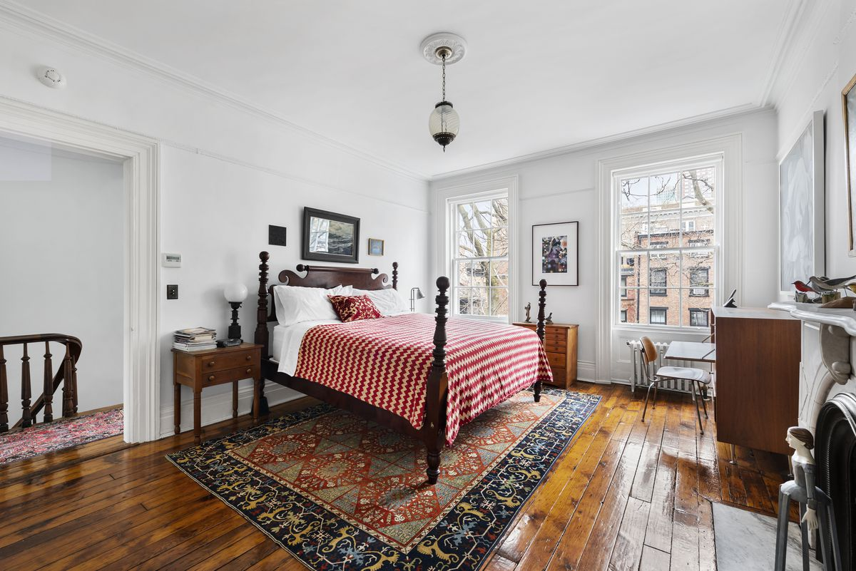 A bedroom with a medium-sized bed, two large windows, a fireplace, and hardwood floors.
