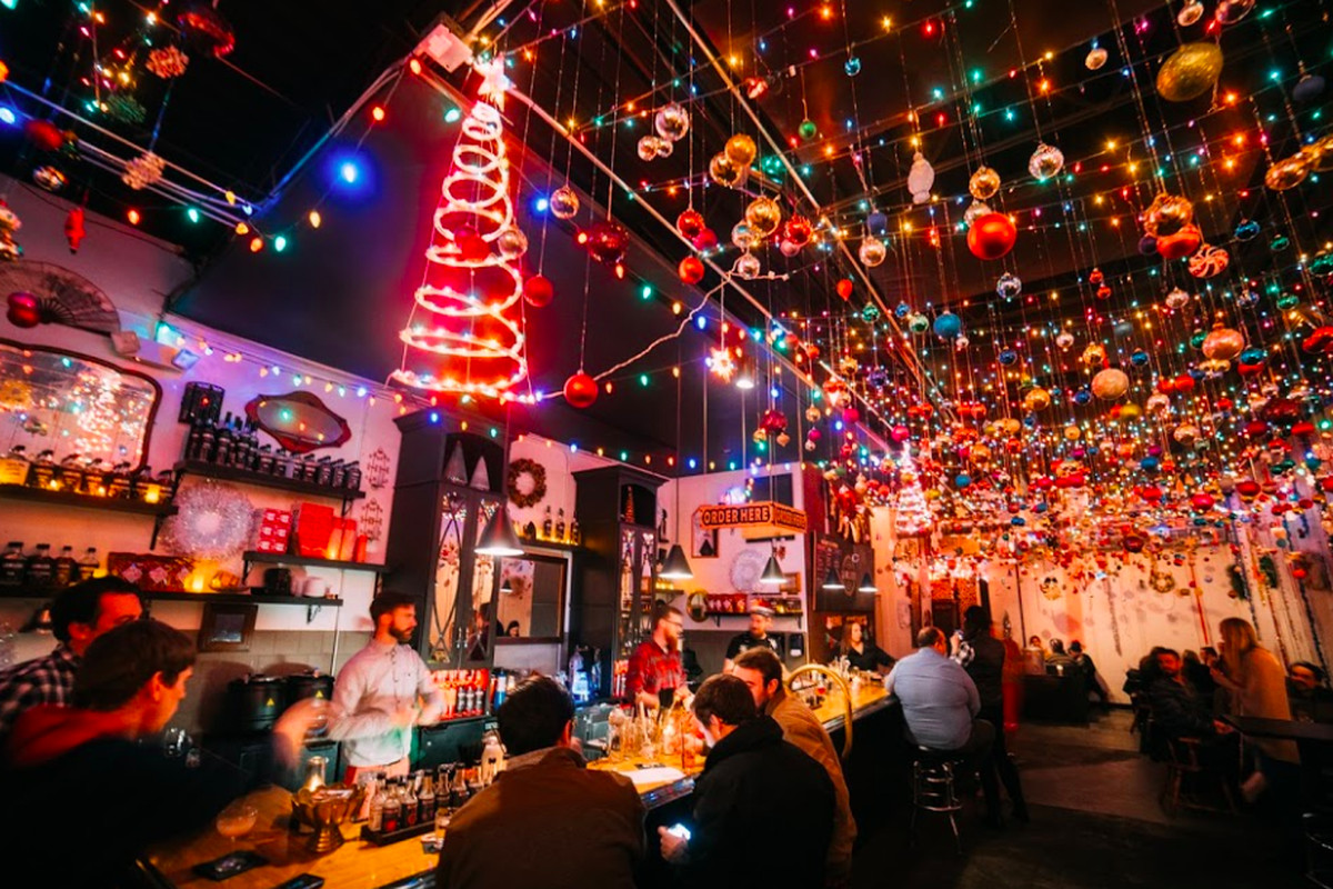 A dark bar full of people and plastered with Christmas decorations, including ornaments dangling from the ceiling.
