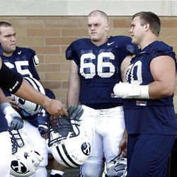 BYU offensive lineman Matt Reynolds, right, who is nursing a hand injury, talks with fellow linemen Houston Reynolds, left, and Andrew Crawford at the start of BYU football practice Thursday in Provo.