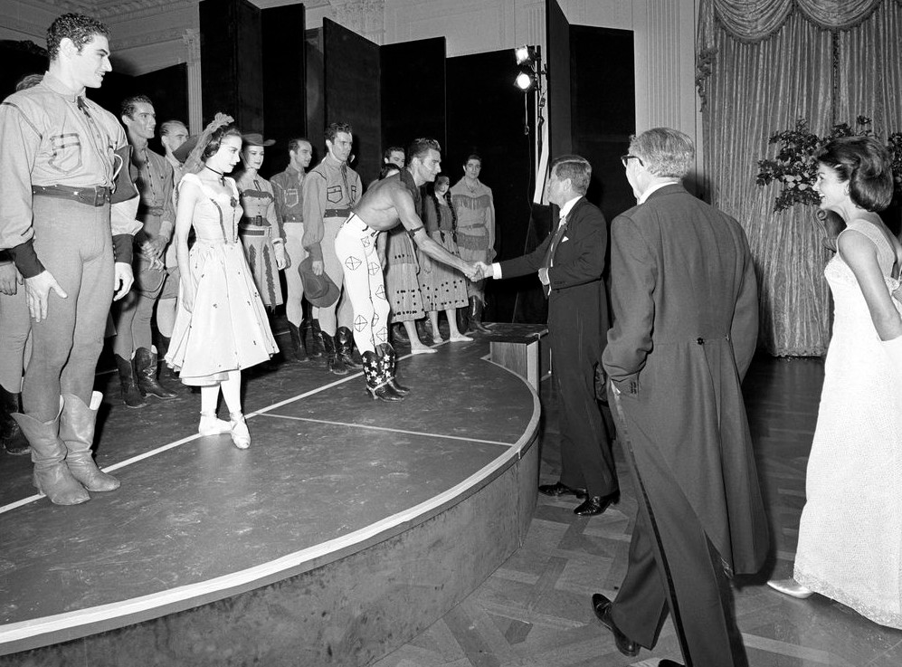 """Ruth Ann Koesun (onstage on left, in lace mantilla and dark choker, toe pointed) with President John F. Kennedy and Jacqueline Kennedy for a 1962 White House performance of the ballet """"Billy the Kid."""" Composer Aaron Copland is in tails, back to camera, on"""
